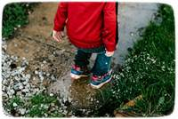 Kid in red jacket jumping in puddle.