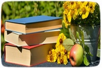Books outside with flowers and an apple.